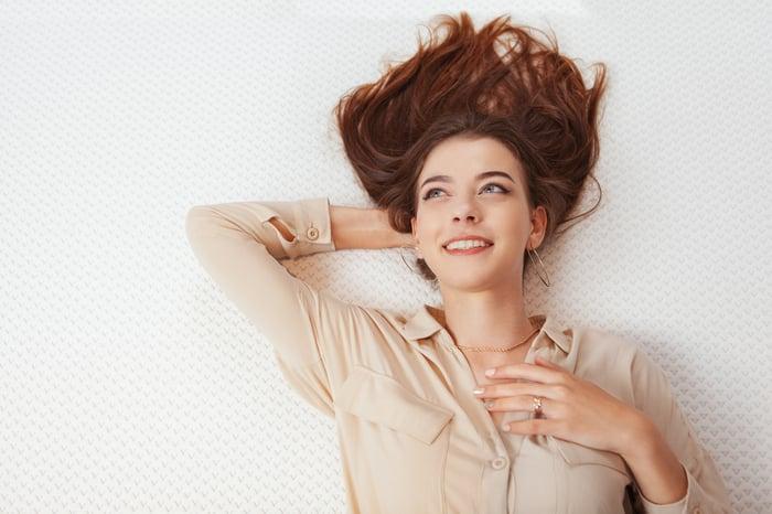 Femme souriante allongée sur un matelas.