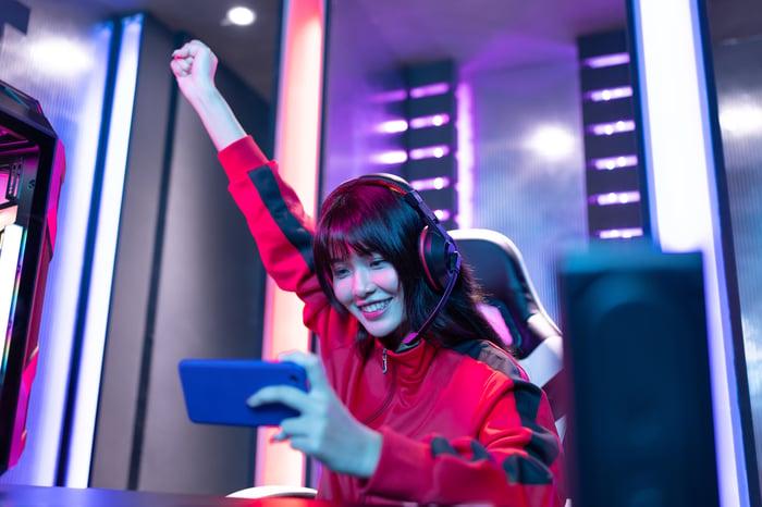 Une femme brandissant son poing droit en l'air lors d'un tournoi de jeu, tout en tenant un smartphone dans sa main gauche.
