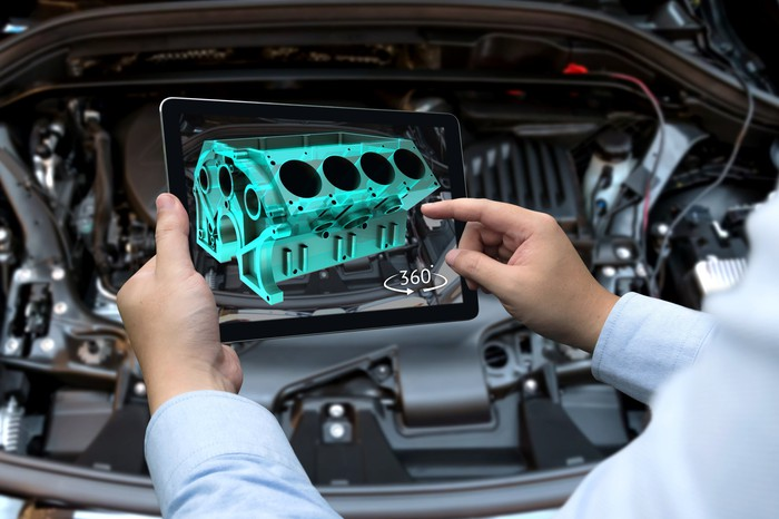 A technician holds a tablet with a 3D model of a car engine.