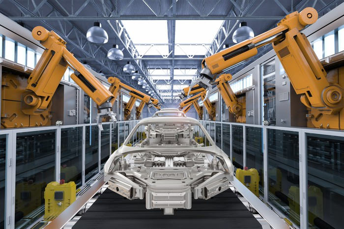 A car body on a conveyor belt surrounded by robotic arms.