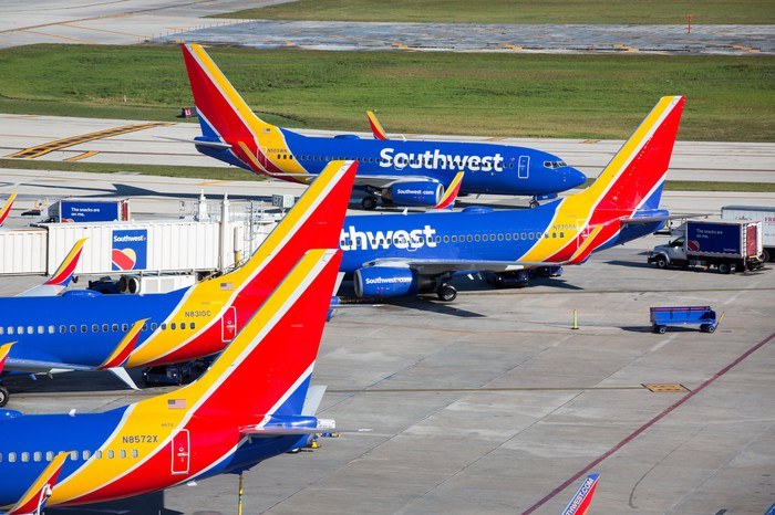 Several Southwest Airlines planes in an airport gate area.