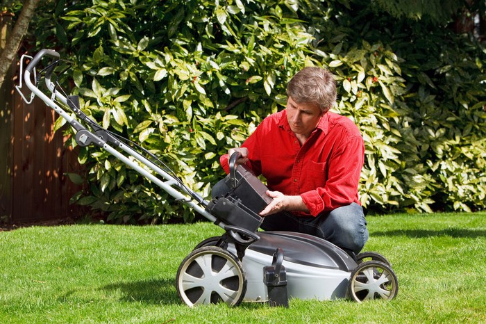Middle-aged man putting a battery into an electric lawnmower.