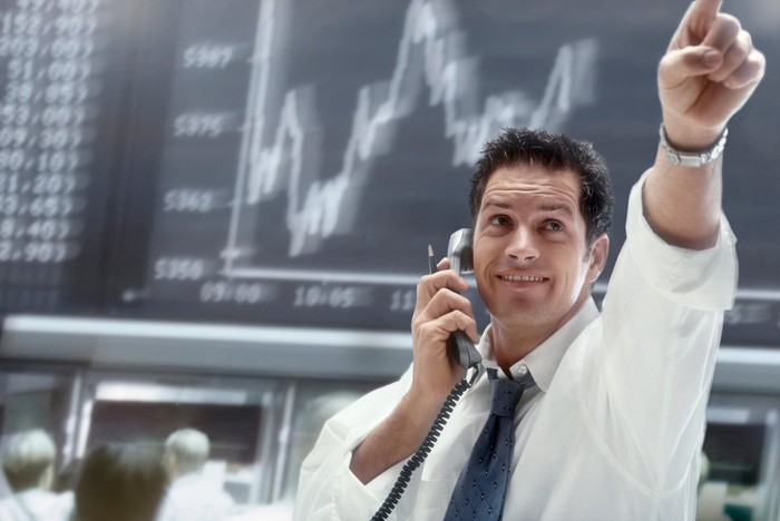 Excited trader pointing up at a stock chart.