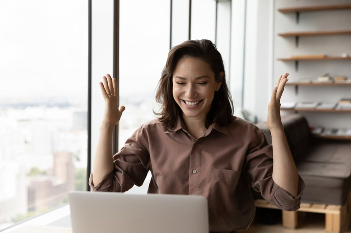 A person celebrates while working on a laptop.
