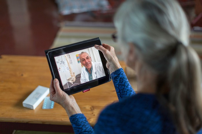 A patient holds a mobile tablet while conducting a virtual care visit.