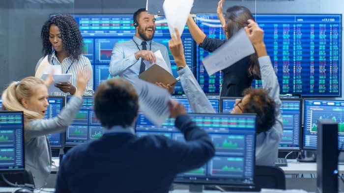 A group of happy people in business attire with screens around them displaying stock market data.