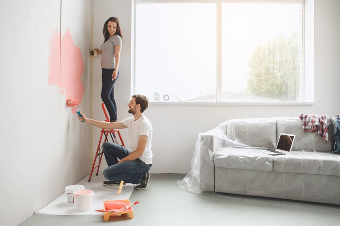 Two people painting a room's walls.