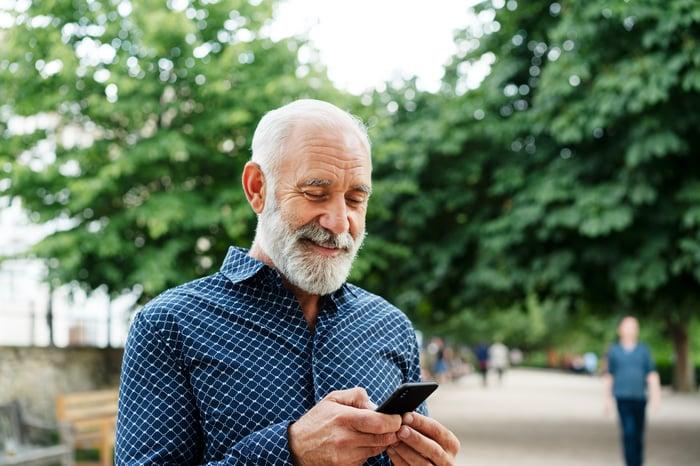 Personne souriante regardant le téléphone à l'extérieur.