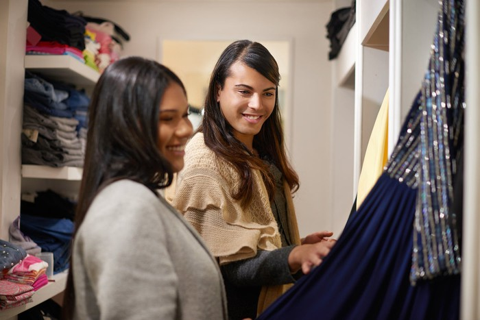 Retailers examine clothes in a store.