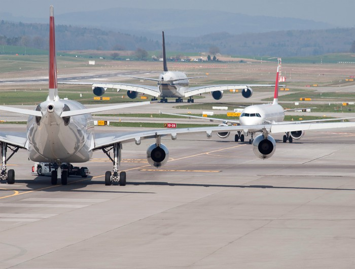Jet airliners parked on a runway.