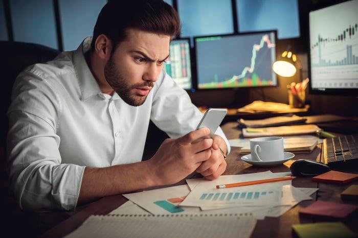 Une personne confuse regarde son téléphone avec des écrans d'ordinateur affichant des graphiques de cours boursiers en arrière-plan.