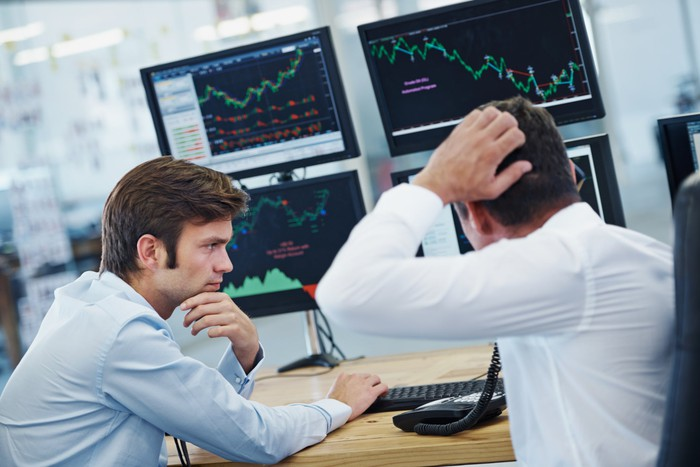 Two concerned persons looking at monitors displaying volatile stock price charts.