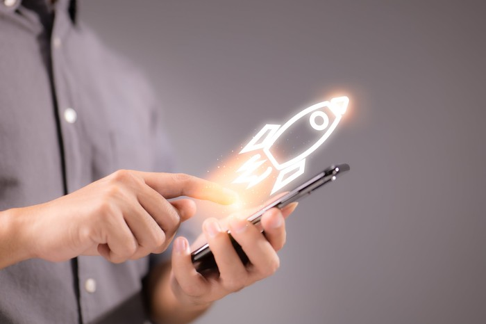 A digital rocket launches off of a smartphone.
