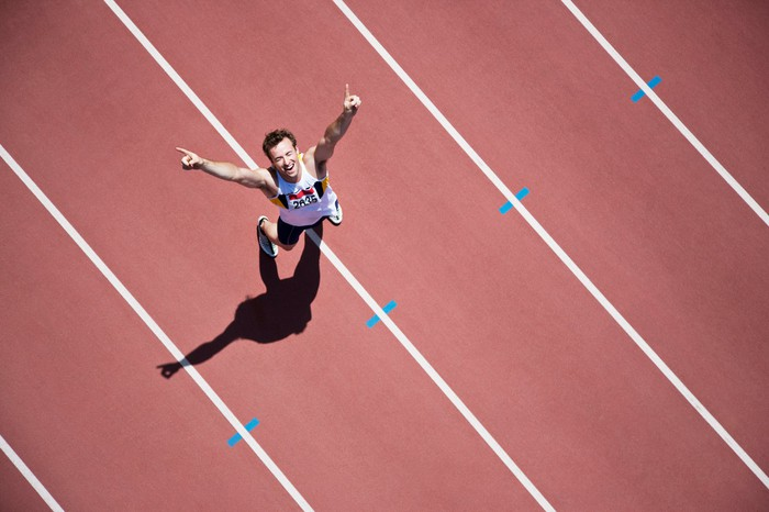 Track athlete with arms in air cheering a victory.