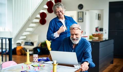 A man sitting at a table with a computer and a woman standing next to him