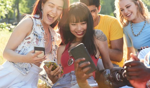 Group of friends laughing while on their phones