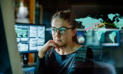 Woman Studies Data on Various Computer Screens
