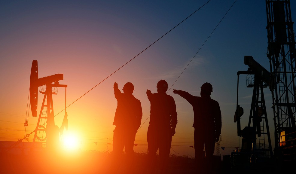 People near an oil well with the sun rising in the background.