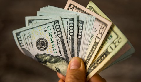 Person Holding Cash Bills Money Hundred Dollar Fifty Dividend Income Invest Retire Spend Getty
