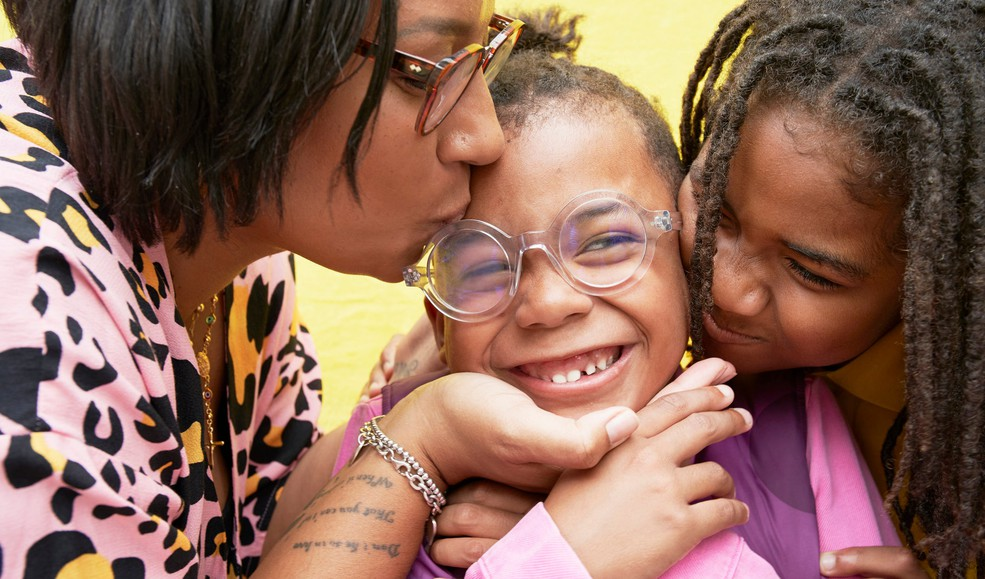 A woman and a girl kissing a little girl in between them