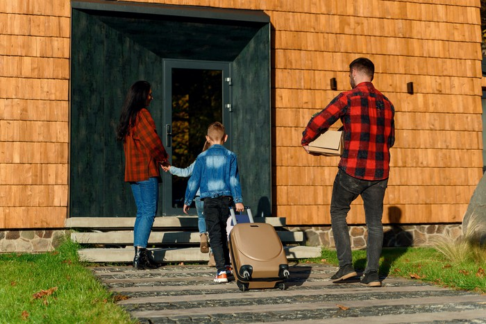 A family walking into a house with their luggage.