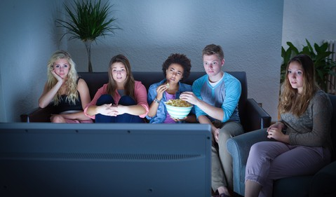 Teenagers Sitting on Sofa and Watching TV