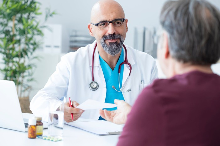 Male doctor talking to a patient in his office.