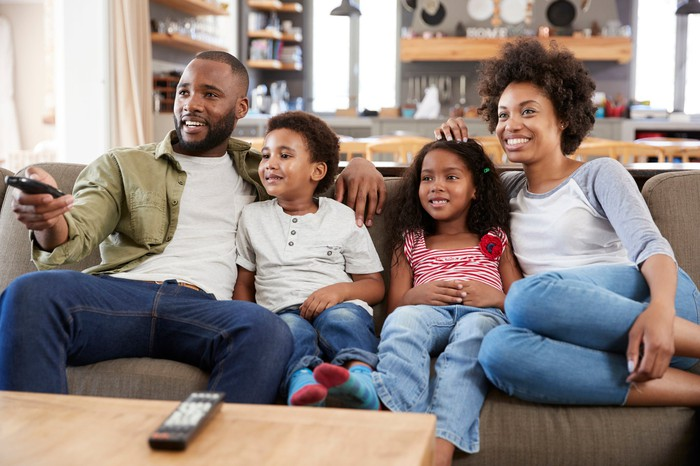 Two parents and two kids on a couch watching TV.