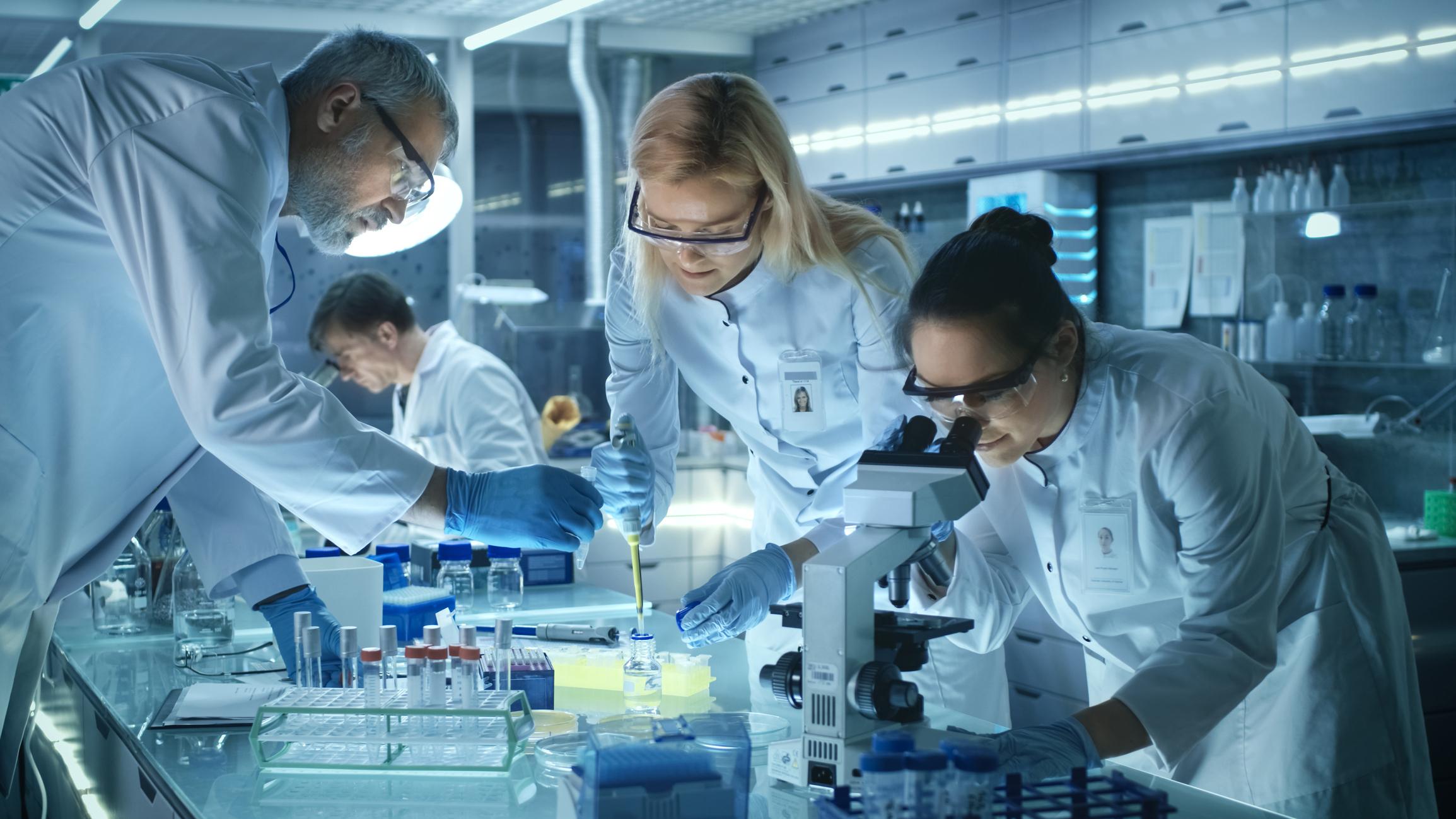 Labatory researchers examine a specimen under a microscope.