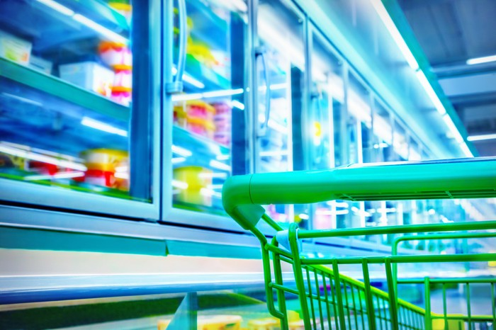 Green shopping cart in frozen food aisle in grocery store