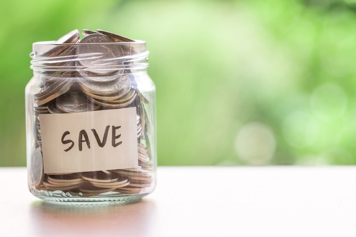 """A jar labelled """"save"""" full of coins."""
