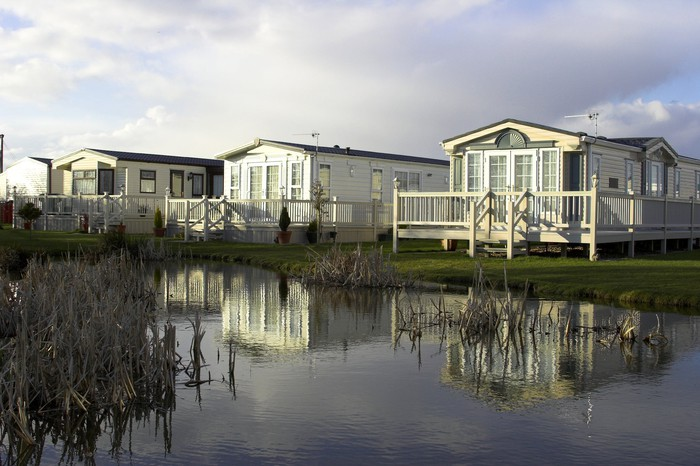 Three manufactured homes next to a pond