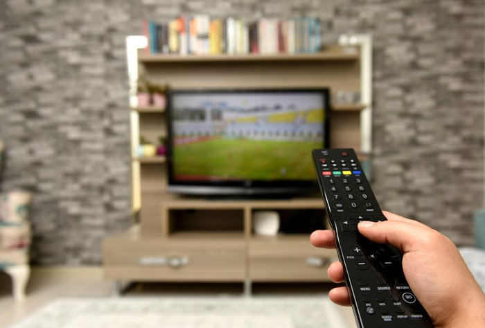 Hand with TV remote in focus, with TV and entertainment console in the background