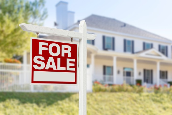 FOR SALE sign in front of house