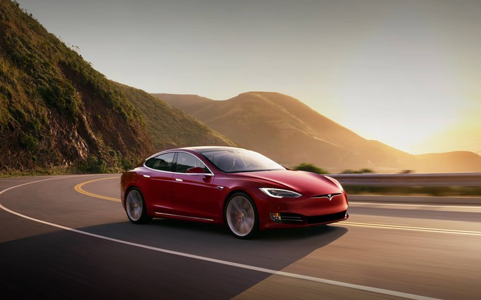 Red Tesla Model S driving along curving road with mountains and sun in the background