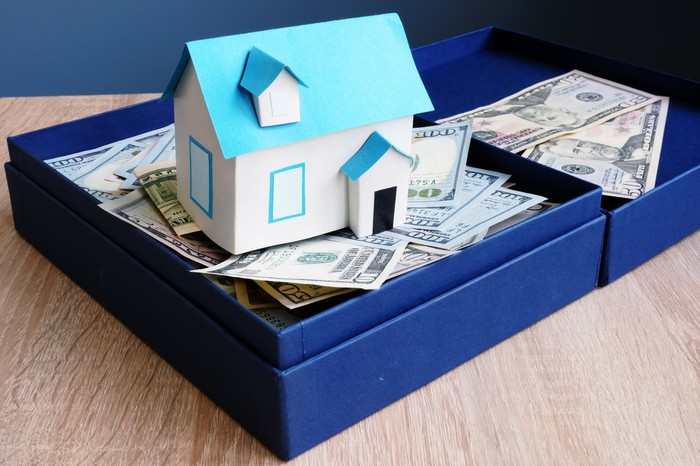 A paper model of a house sitting in a box full of $20, $50, and $100 bills