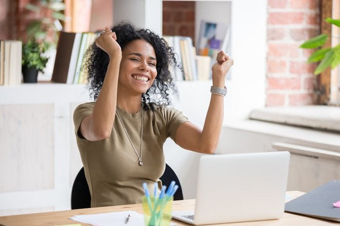 Smiling woman sitting at computer raises both hands in celebration.