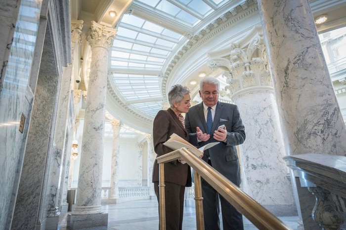Two mature businesspeople discuss financial matters in a federal building.