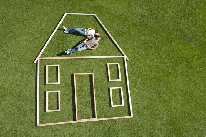 There is a couple lying on grass. An outline of a house in wood surrounds them.