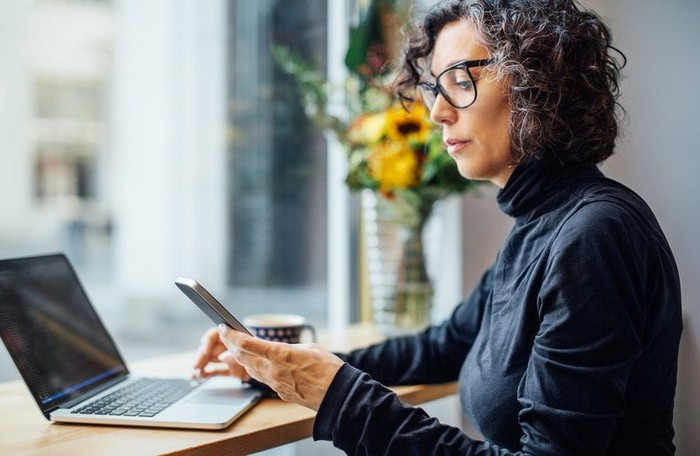 Mature women looking at her cell phone with a laptop in front of her.