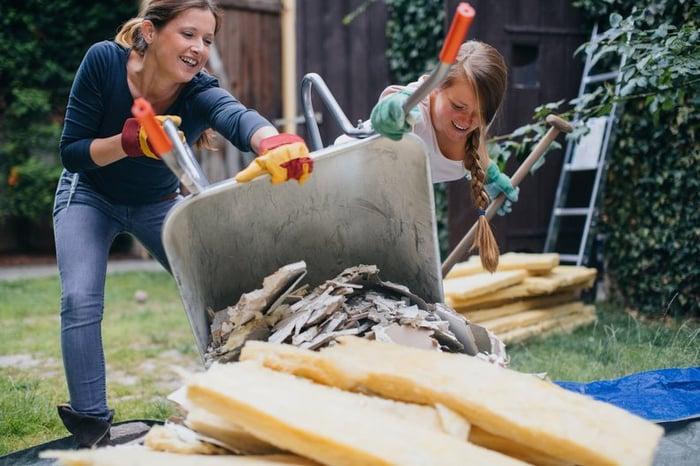 Deux femmes jettent des déchets de rénovation domiciliaire dans un tas à l'extérieur
