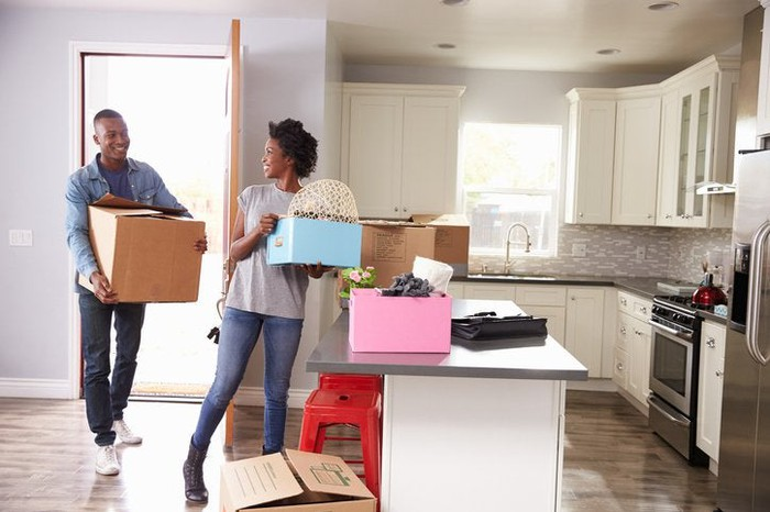 A man and woman carrying boxes into the kitchen of their new home.