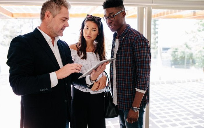 A young man and woman speaking with their realtor who's holding a tablet in an open house.