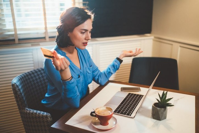 A woman looking frustrated with a credit card in her hand while looking at a laptop.