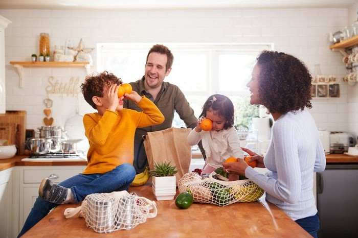 A mom, dad, son, and daughter unpacking bags of groceries in their kitchen and playing with the food.