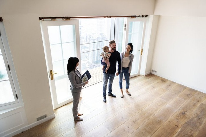 A man and woman with their young daughter touring an empty living room with a realtor.