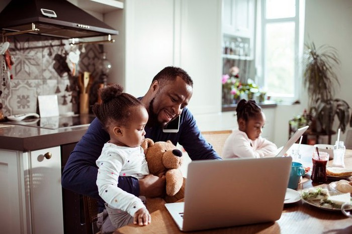 A father working on his laptop while managing two young children.
