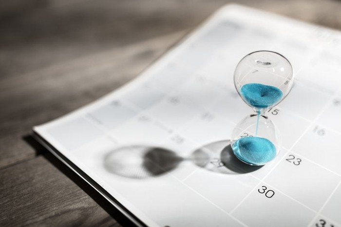 An hourglass filled with blue sand sitting on top of a calendar page on a wooden desk.