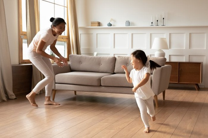 A smiling mother and her young daughter playing and chasing each other in their living room.