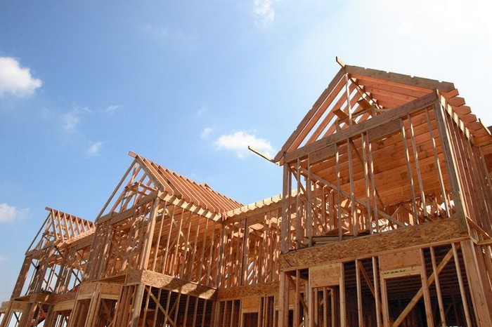 The wooden frame of a new home under construction in front of a blue sky.